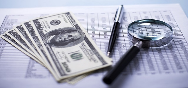 Conceptual image of fanned dollar banknotes with a magnifying glass, pen and analytical financial report lying on a table with shallow dof