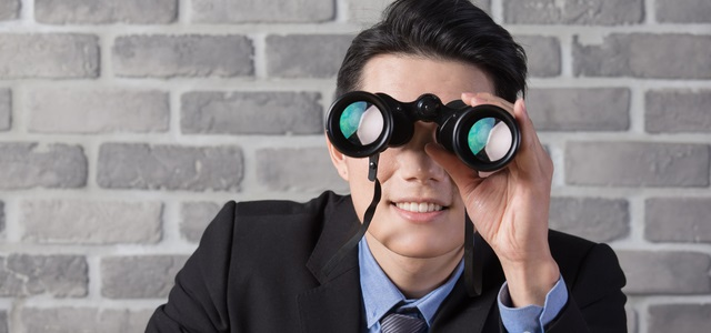 business man use binocular with brick wall in office,asian